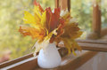 Autumn mapple leaves bunch maple in vase on old wooden windowsill Royalty Free Stock Image
