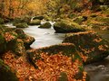 Autumn mountain river with blurred waves fresh green mossy stones colorful fall view into and boulders on bank covered Stock Photo