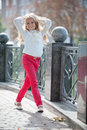 Autumn in the park blonde girl shows clothing red jeans and a white blouse Royalty Free Stock Photography