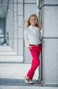Autumn in the park blonde girl shows clothing red jeans and a white blouse Stock Photography