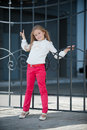 Autumn in the park blonde girl shows clothing red jeans and a white blouse Royalty Free Stock Image