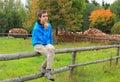 Teenage boy sitting on a fence