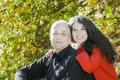Autumn park outdoor family portrait of smiling adult daughter hugging her senior father