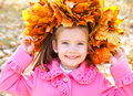 Autumn portrait of cute smiling little girl having fun in the park Royalty Free Stock Image
