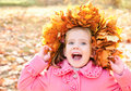 Autumn portrait of little girl in maple wreath screaming outdoors Royalty Free Stock Photo