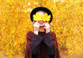 Autumn portrait smiling woman wearing a black hat and knitted poncho over sunny yellow leaves background Royalty Free Stock Photo