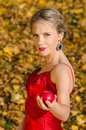 Autumn portrait of young pretty woman with basket of apples holding an apple Stock Photo