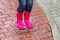 Autumn. Protection in the rain. Girl wearing pink rubber boots and jumping into a puddle. Royalty Free Stock Photo