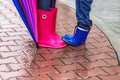 Autumn. Protection in the rain. Woman wearing pink rubber boots with umbrella and her child having fun in the rainy day. Royalty Free Stock Photo