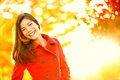 Autumn red trench coat woman in sun flare foliage Stock Images