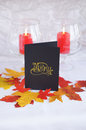 Autumn s menu black with gold type red and yellow paper leaves and red candles in glasses Royalty Free Stock Photography