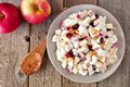 Autumn saladwith chicken, apples, nuts and cranberries, over wood Royalty Free Stock Photo