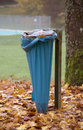 Autumn scenery with refuse sack including a tree trunk a small lake and a Stock Photography