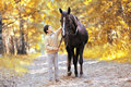 Autumn season happy teenager boy and horse walking Royalty Free Stock Photo