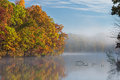 Autumn shoreline eagle lake of in fog with reflections in calm water fort custer state park michigan usa Stock Images