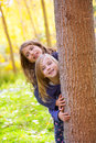Autumn sister kid girls playing in forest trunk outdoor Stock Photos