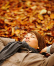 Autumn - Smiling woman lying peacefully on leaves Stock Photo
