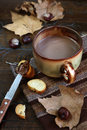 Autumn still life chestnuts cocoa and chocolate spread on a sl mood leaf litter slice of baguette Royalty Free Stock Images