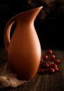 Autumn still life with jug leaf and rosehip wooden background Stock Image