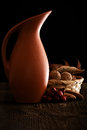 Autumn still life with jug walnut almond and rosehip wooden background Stock Images
