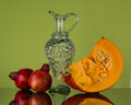 Autumn still life with pumpkin and two pomegranate. Royalty Free Stock Photo