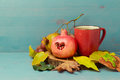 Autumn still life with red tea cup, pomegranate and leaves Royalty Free Stock Photo