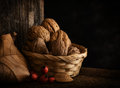 Autumn still life with walnut leaf and rosehip wooden background braided basket Stock Photo