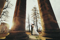 Autumn sun shines above a weddding couple which stands between o Royalty Free Stock Photo