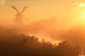 Autumn sunrise foggy and colorful at a traditional dutch windmill Stock Photo