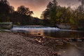 Autumn sunset over the river and weir waterfall called viktorcin splav in babiccino udoli grandmas valley czech republic Stock Photos