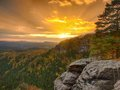Autumn sunset view over sandstone rocks to fall colorful valley of Bohemian Switzerland. Sandstone peaks in forest. Royalty Free Stock Photo