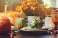 Autumn traditional table setting for Thanksgiving or Halloween, with candles, flowers and pumpkins. Royalty Free Stock Photo