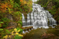 Autumn waterfall hector falls in new york surrounded by trees and plants with peak fall colors a beautiful roadside just north of Stock Photography
