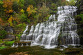 Autumn waterfall hector falls in new york surrounded by trees and plants with peak fall colors a beautiful roadside just north of Royalty Free Stock Images