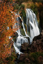 Autumn waterfall with orange leaves detail of Royalty Free Stock Photo