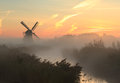 Autumn windmill just before sunrise at a dutch on a foggy morning in Stock Images