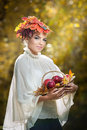 Autumn woman beautiful creative makeup and hair style in outdoor shoot girl with leaves in hair holding a basket with apples Stock Image