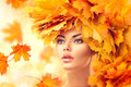 Autumn woman. Beauty model girl with autumn bright leaves hairstyle Royalty Free Stock Photo