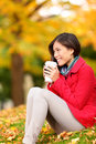 Autumn woman drinking coffee in fall forest girl sitting relaxing enjoying hot drink or tea from disposable cup beautiful Royalty Free Stock Image