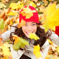 Autumn woman happy with colorful fall leaves falling in forest foliage excited cheerful girl looking at camera joyful Royalty Free Stock Images