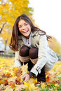 Autumn woman playing with colorful fall leaves in city park smiling happy and excited stylish modern brunette close up portrait of Stock Image
