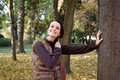 Autumn woman wearing fur vest leaning tree in the park Stock Image