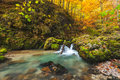 Autumnal creek with beautiful mossy stones and blue water in transylvania Royalty Free Stock Image