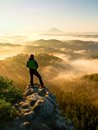 Autumnal  misty morning in nature. Hiker in black stand on peak in rock Royalty Free Stock Photo