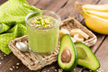 Avocado and banana smoothie with oats with ingredients in glass jar on wooden background Royalty Free Stock Photo