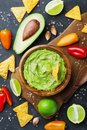 Avocado guacamole with  ingredients pepper, lime and nachos on black table top view. Traditional mexican food. Royalty Free Stock Photo