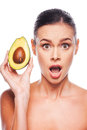 Avocado surprised young shirtless woman holding in her hand and keeping mouth open while standing against white background Royalty Free Stock Photography