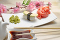 Avocado sushi nigiri on white plate with ginger wasabi and soy sauce decorated with sakura and chopsticks Royalty Free Stock Photos
