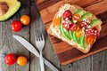 Avocado toast with hummus and tomatoes on server, above scene on wood Royalty Free Stock Photo