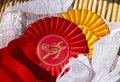 Award rosettes in equestrian sport, red and yellow. Prize ribbons for horse show, champion competition. Royalty Free Stock Photo